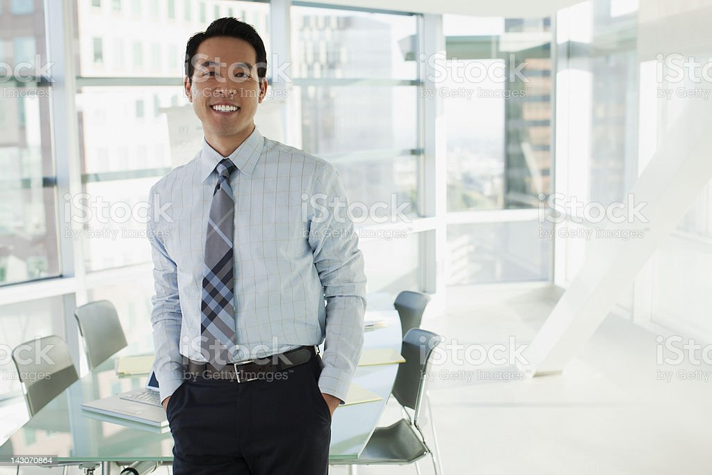 Smiling businessman standing in office stock photo