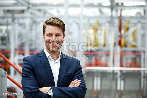 Portrait of smiling male manager working at automobile industry. Confident handsome businessman is standing with arms crossed at factory. He is wearing businesswear.