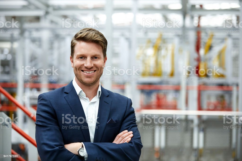 Smiling businessman standing with arms crossed stock photo