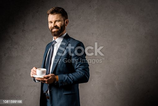 1081599130 istock photo smiling businessman standing with cup of coffee 1081599166