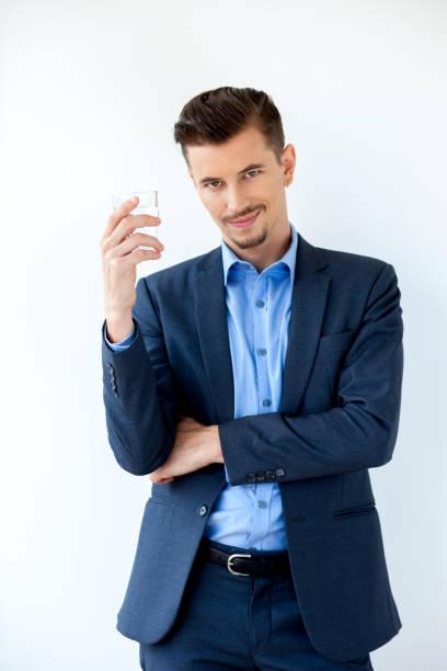 smiling businessman standing with water glass - leitungswasser trinken stock-fotos und bilder