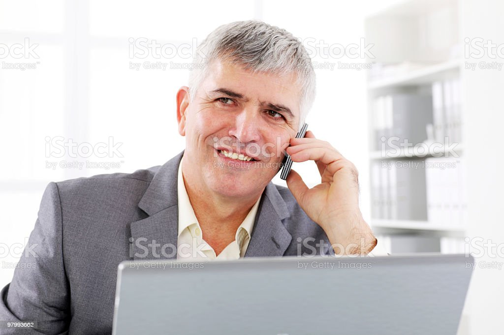 Smiling businessman talking by mobile phone in the office. royalty-free stock photo