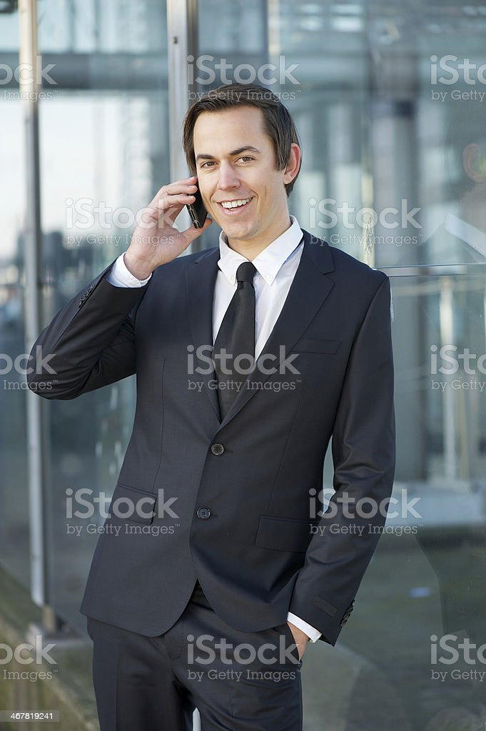 Smiling businessman talking on mobile phone outdoors royalty-free stock photo