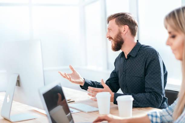 lächelnder Geschäftsmann im Gespräch mit einem Kollegen, der an seinem Schreibtisch sitzt – Foto