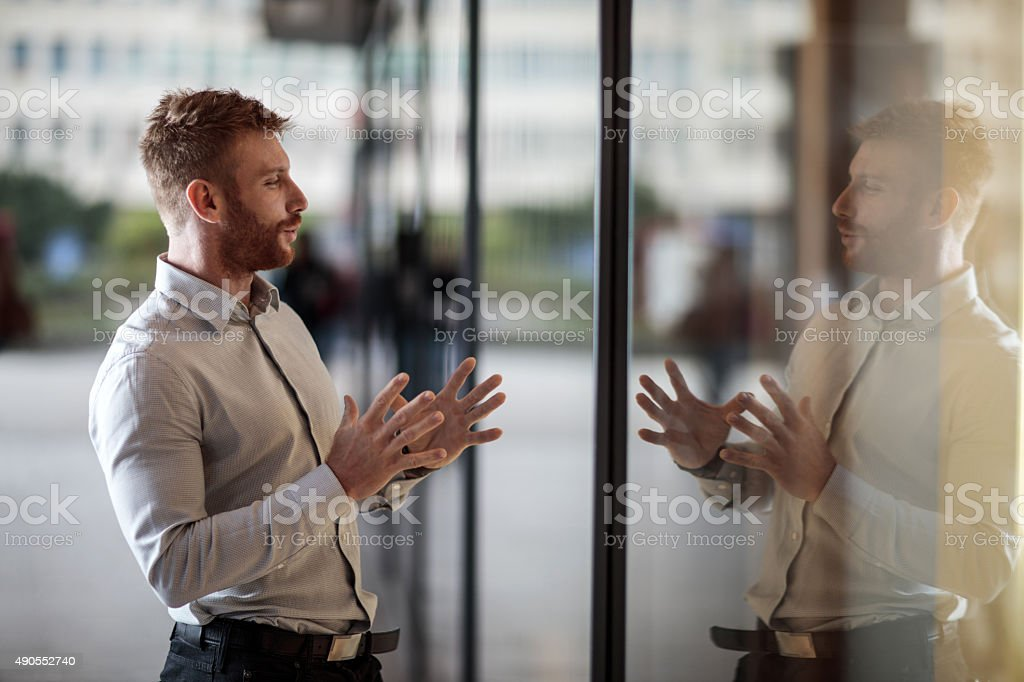 Smiling businessman talking to his reflection in window display. stock photo