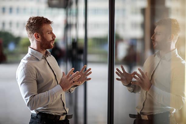 Lächelnd Geschäftsmann Gespräch auf seinem Reflektion im Fenster angezeigt. – Foto