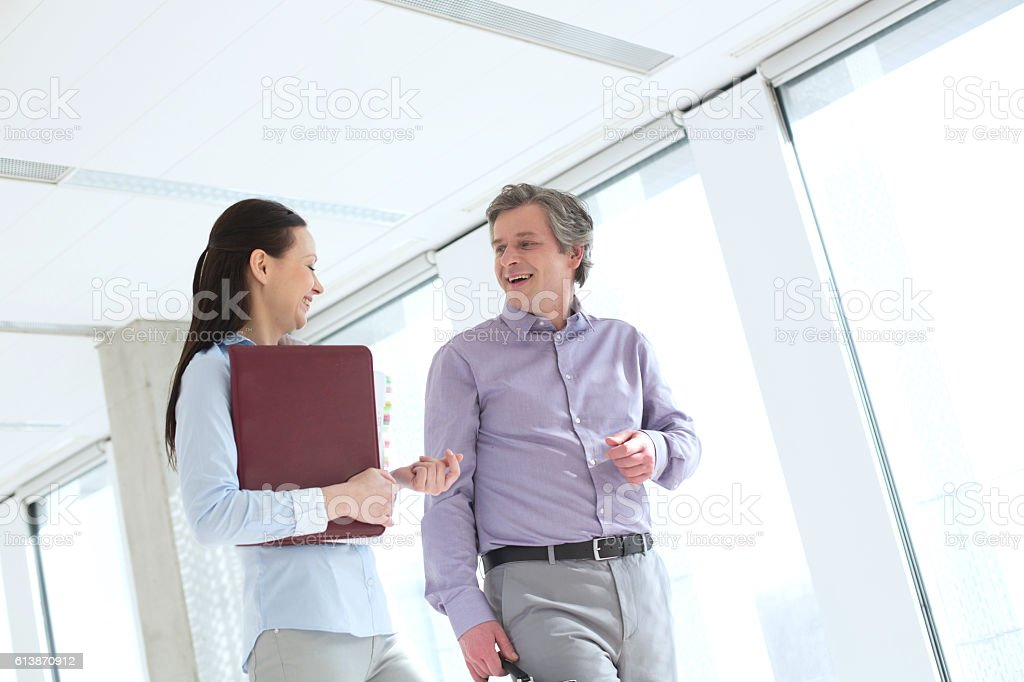 Smiling businessman talking with female colleague in office stock photo