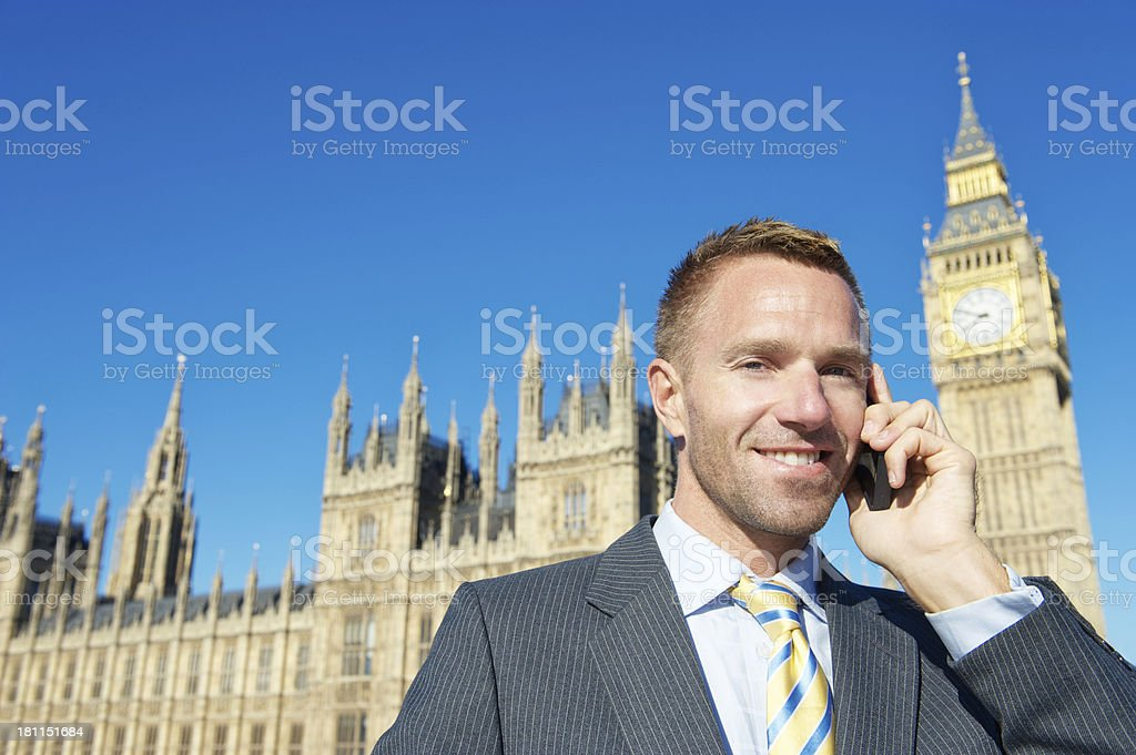 Smiling Businessman Talks on Mobile Phone Houses of Parliament London royalty-free stock photo