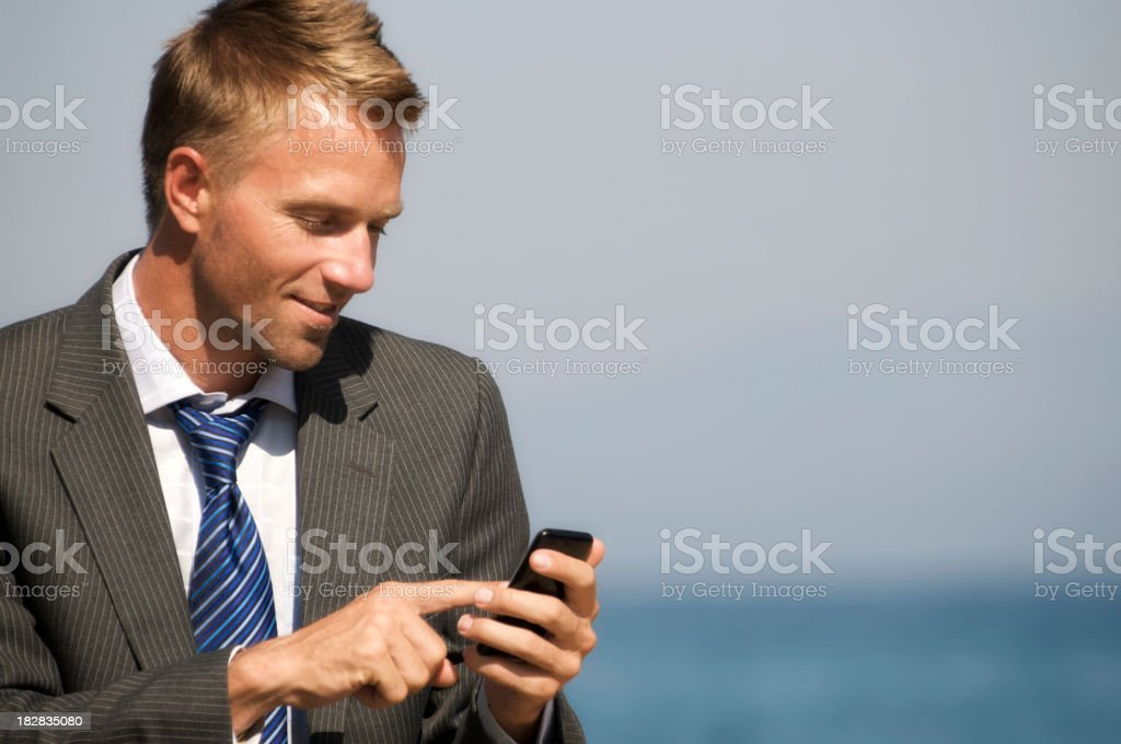 Smiling Businessman Texts by the Sea royalty-free stock photo