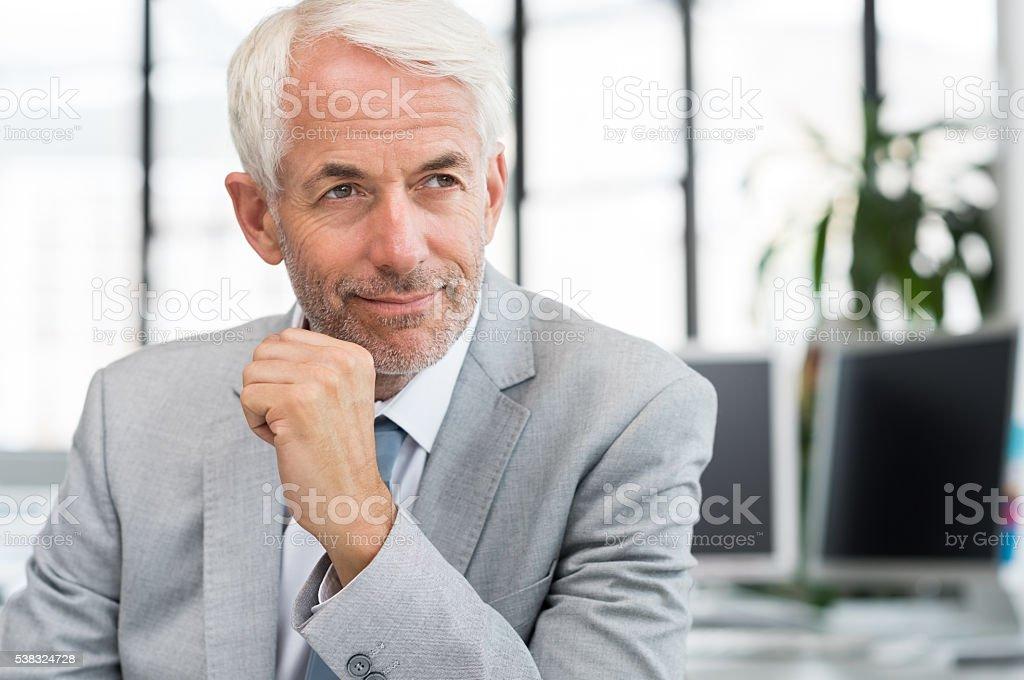 Smiling businessman thinking stock photo