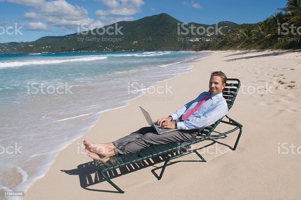 Smiling Businessman Typing Outdoors on Beach Chair royalty-free stock photo
