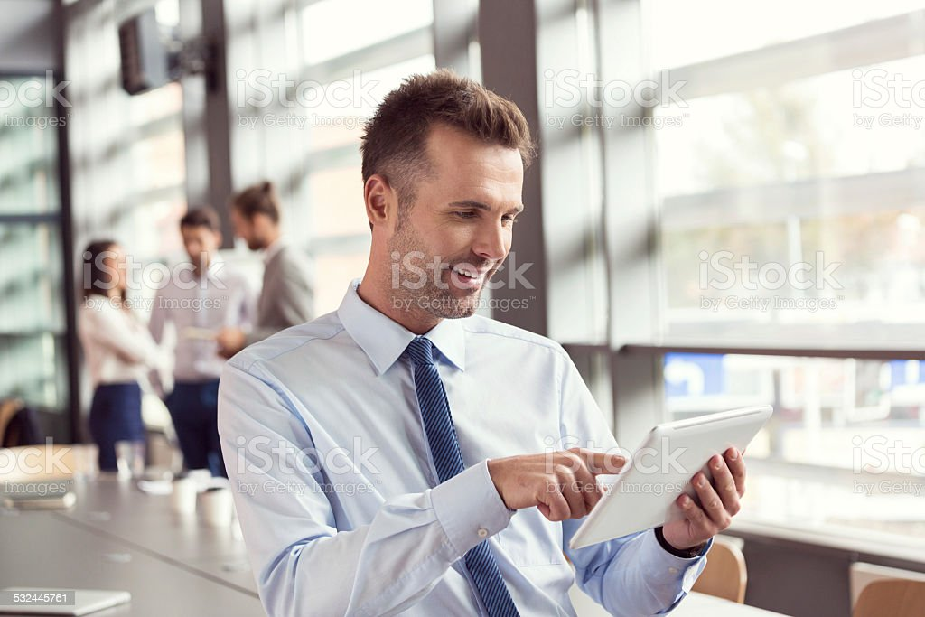 Smiling businessman using a digital tablet in an office Portrait of confident businessman wearing shirt and tie using a digital tablet in an conference room. Coworkers talking in the background. 2015 Stock Photo