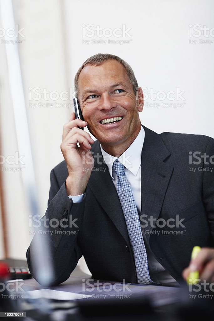 Smiling businessman using a mobile phone at office royalty-free stock photo