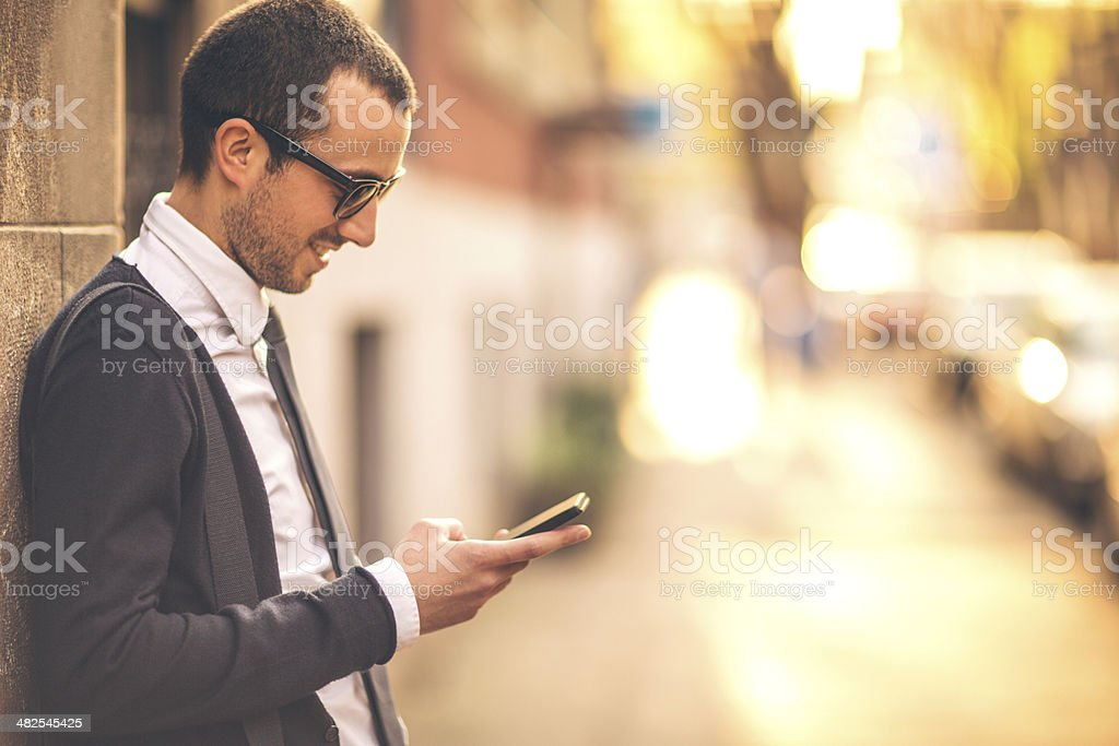 Smiling businessman using a smartphone on the street stock photo