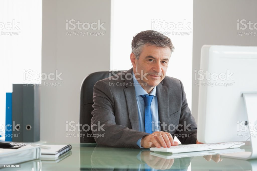 Smiling businessman using computer at office stock photo