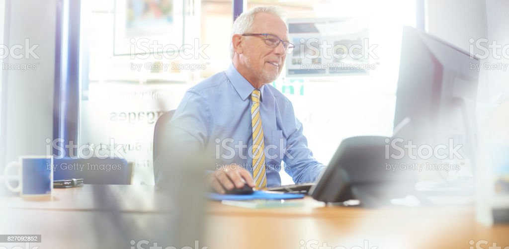 Smiling businessman using computer stock photo