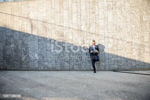 istock Smiling businessman using digital tablet 1037138236