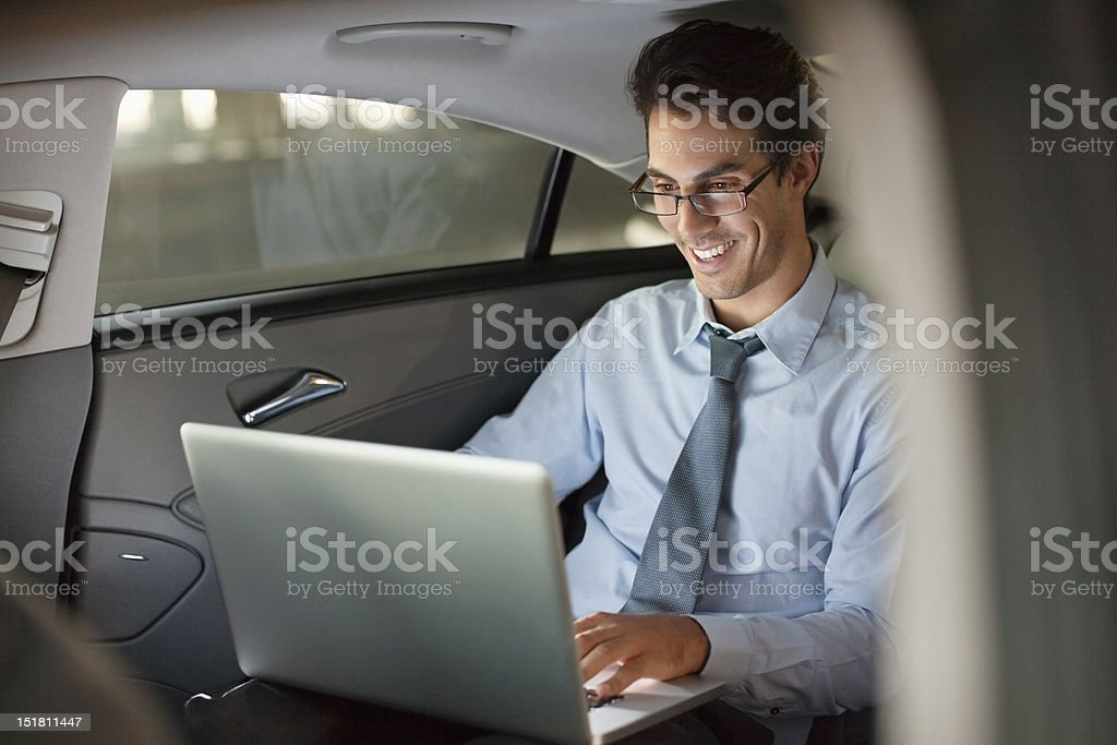 Smiling businessman using laptop in back seat of car at night royalty-free stock photo