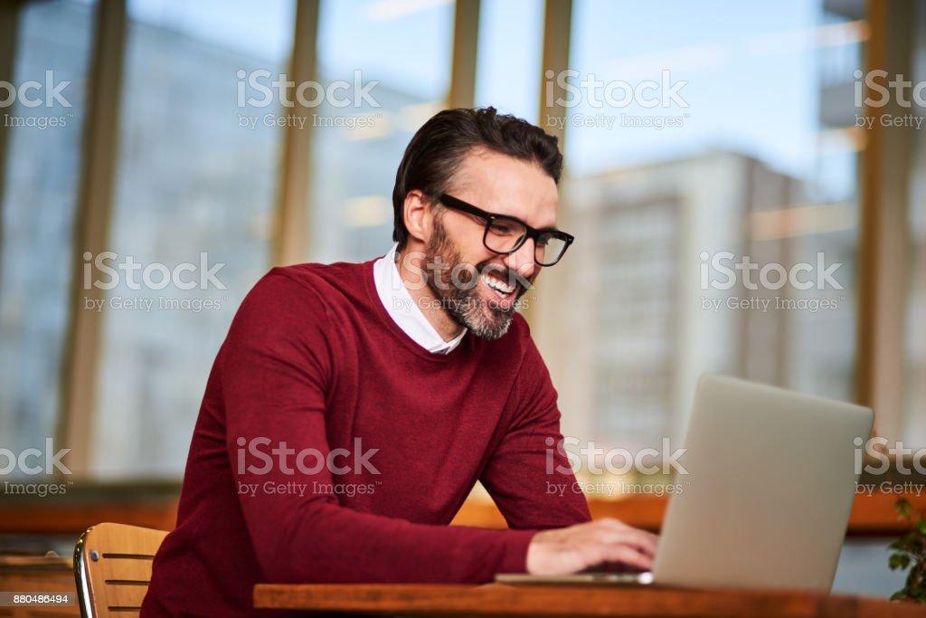 Smiling businessman using laptop stock photo