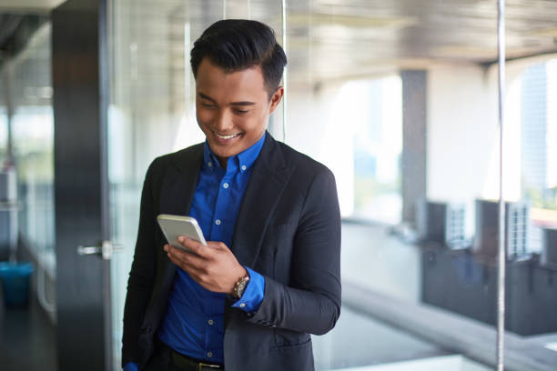 Smiling businessman using mobile phone in office stock photo