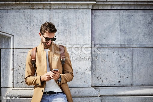 istock Smiling businessman using phone against building 691910409