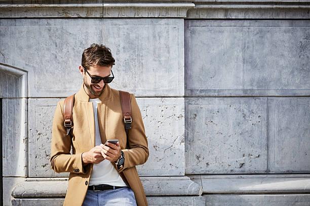 smiling businessman using phone against building - spain solar bildbanksfoton och bilder