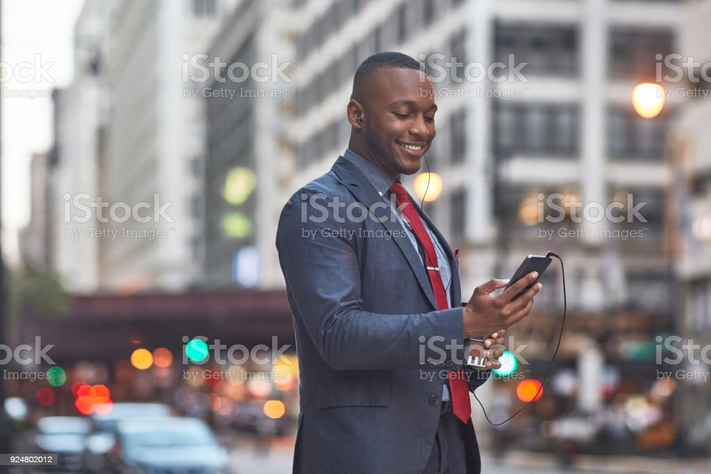 Smiling businessman using smart phone in city stock photo