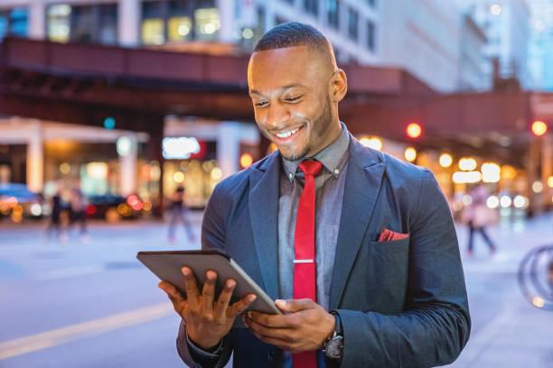 lächelnde geschäftsmann mit tablet computer chicago straßen - gute nacht text stock-fotos und bilder