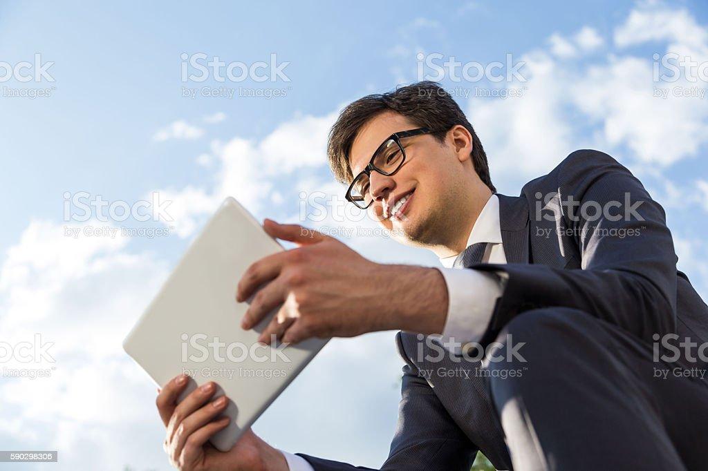 Smiling businessman using tablet outside royaltyfri bildbanksbilder