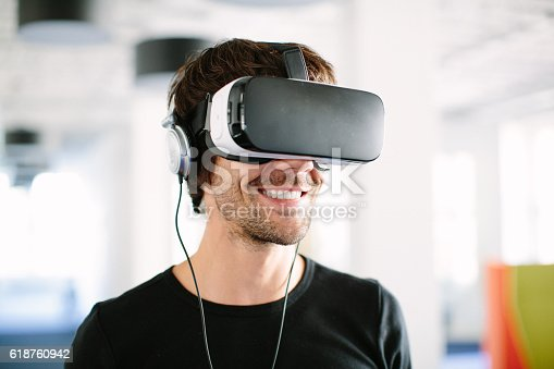 Closeup shot of smiling young man using virtual reality glasses in office
