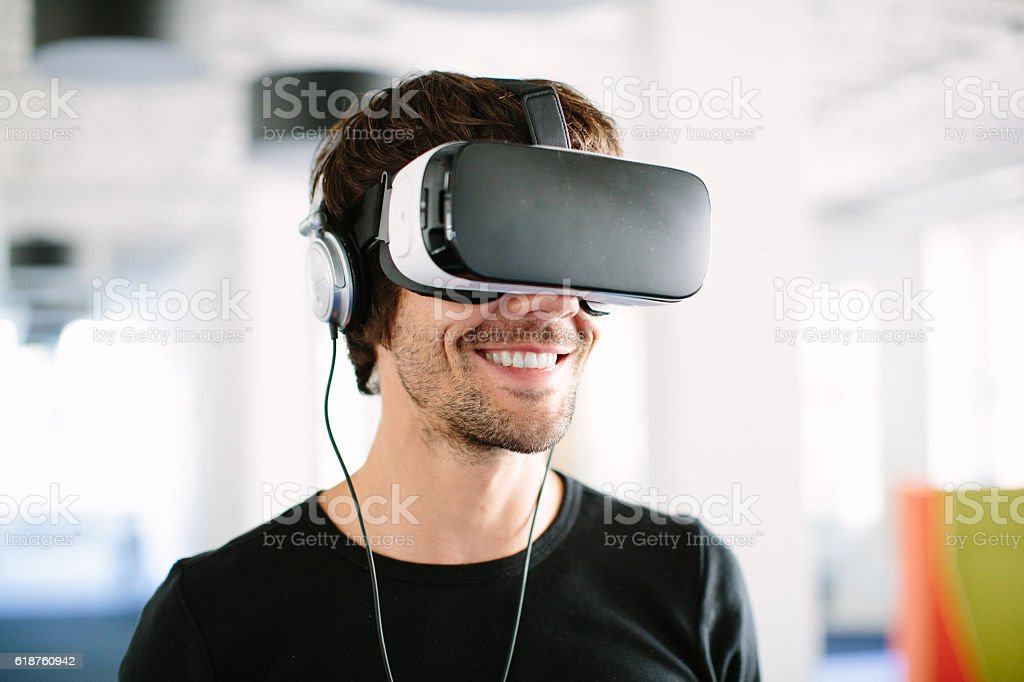 Smiling businessman using VR simulator in office stock photo