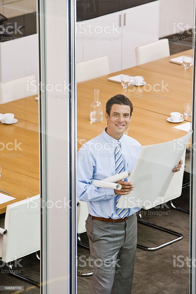 Smiling businessman viewing blueprints at conference room window royalty-free stock photo