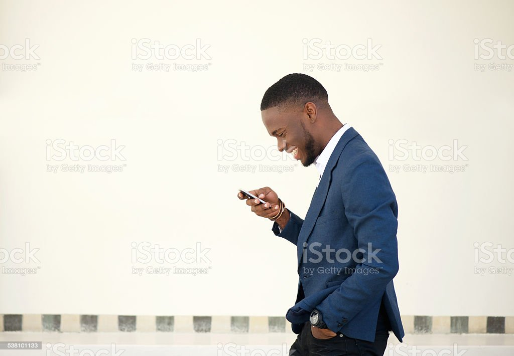 Smiling businessman walking and sending text message stock photo