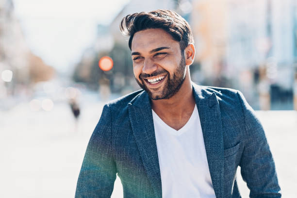 Smiling businessman walking outdoors in the city Happy young man walking outdoors in the city looking away stock pictures, royalty-free photos & images