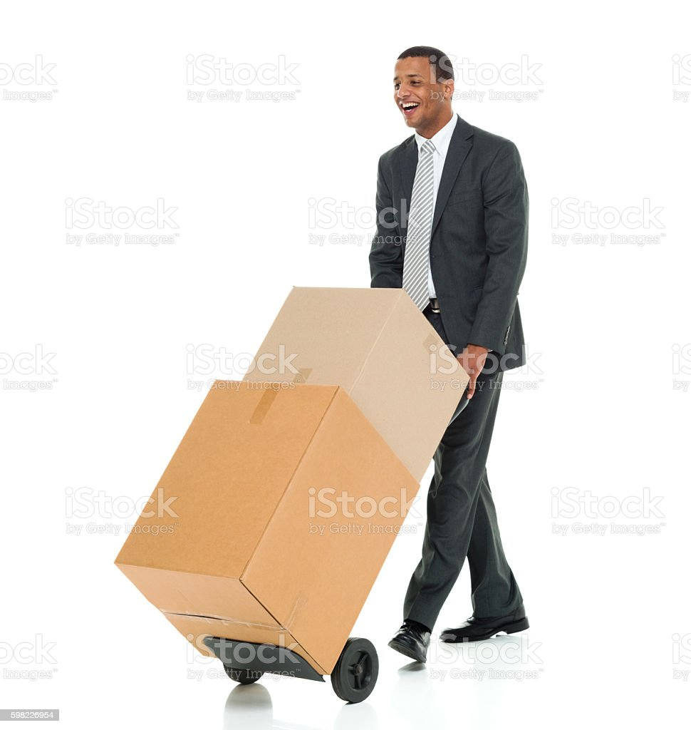 Smiling businessman walking with hand truck foto royalty-free