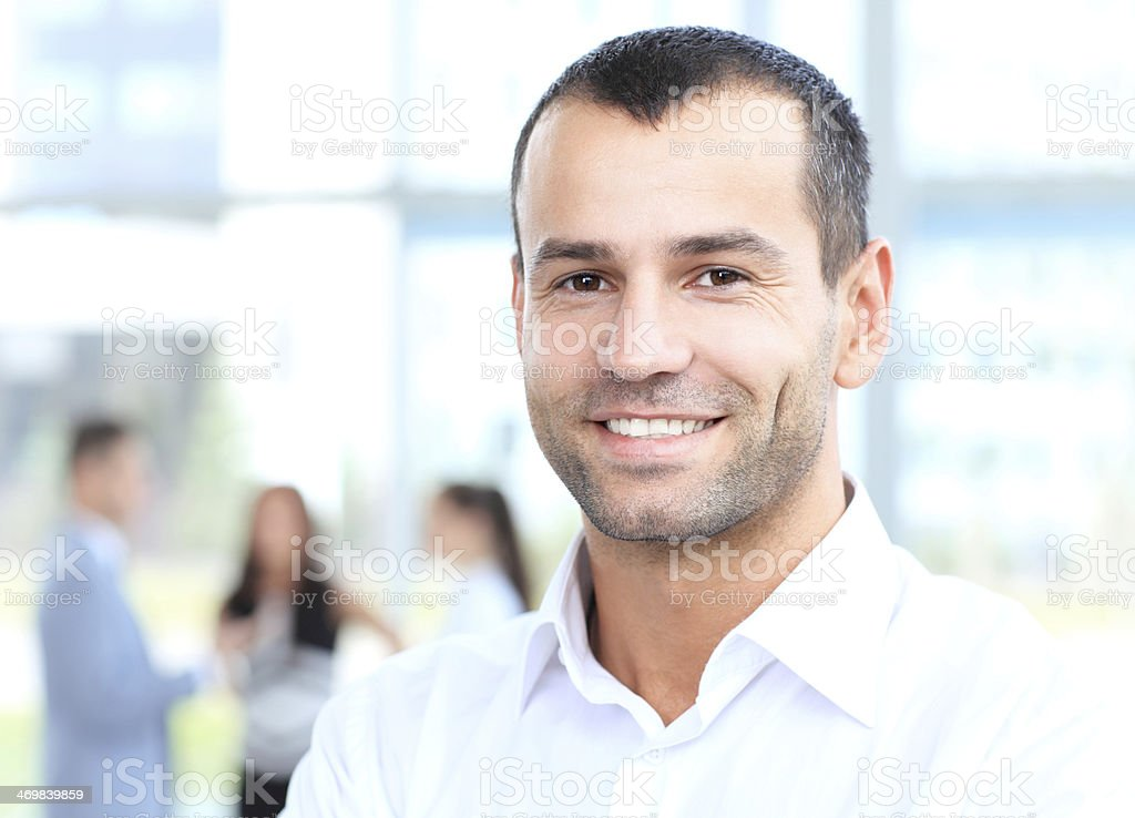 Smiling businessman with a blurred background of colleagues stock photo