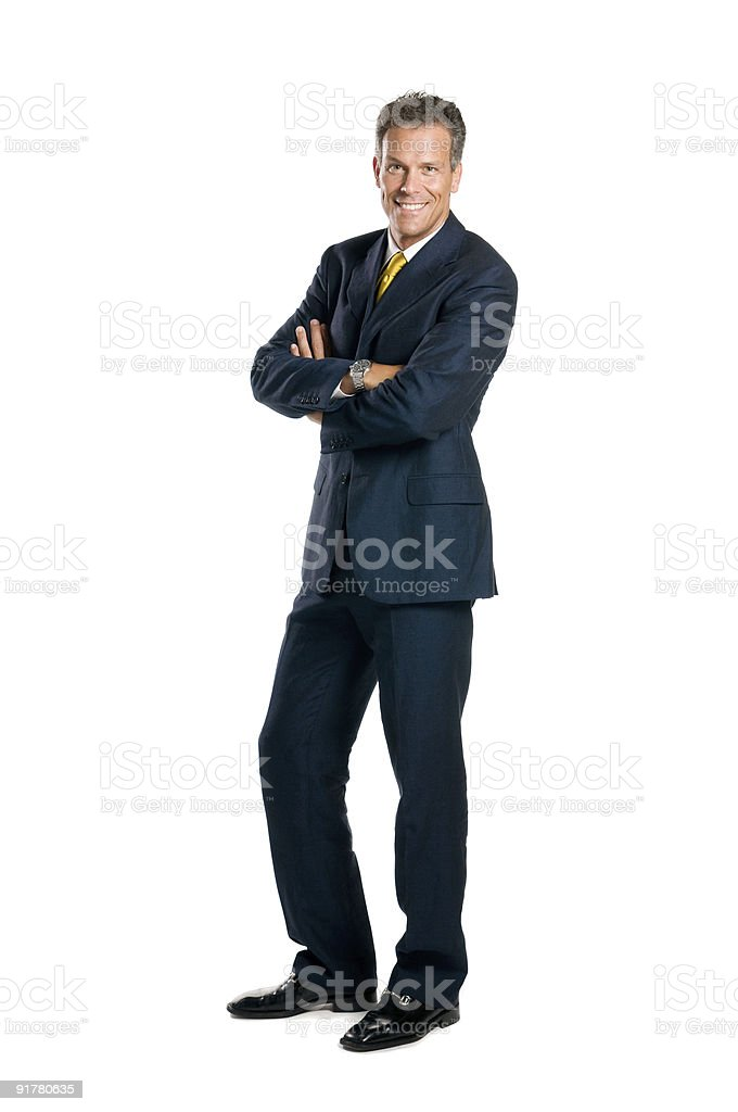 A smiling businessman with arms crossed wearing a suit stock photo