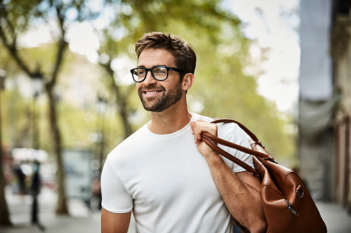 Smiling handsome businessman with beard walking in city. Executive is looking away while carrying bag. He is wearing eyeglasses.