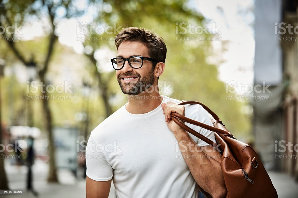 Smiling businessman with brown bag walking in city stock photo