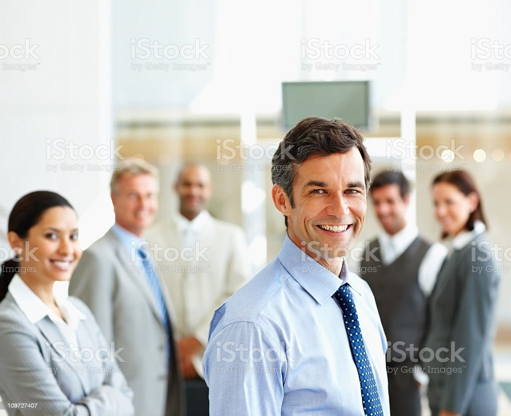 Smiling businessman with colleagues in the background stock photo