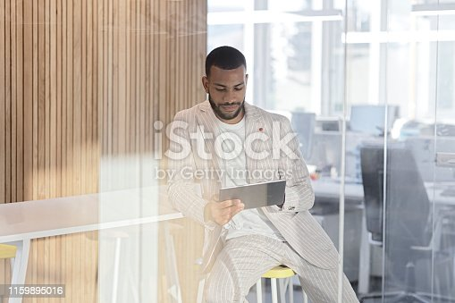 istock Smiling businessman  with digital tablet 1159895016