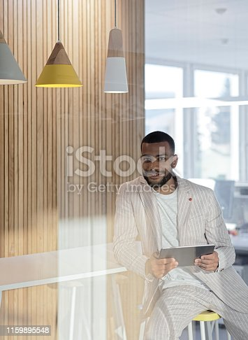 istock Smiling businessman  with digital tablet 1159895548