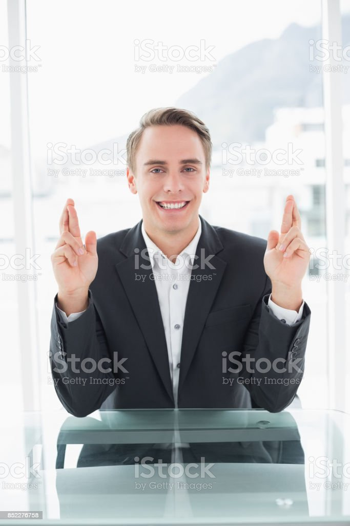 Portrait of a smiling young businessman with fingers crossed sitting...