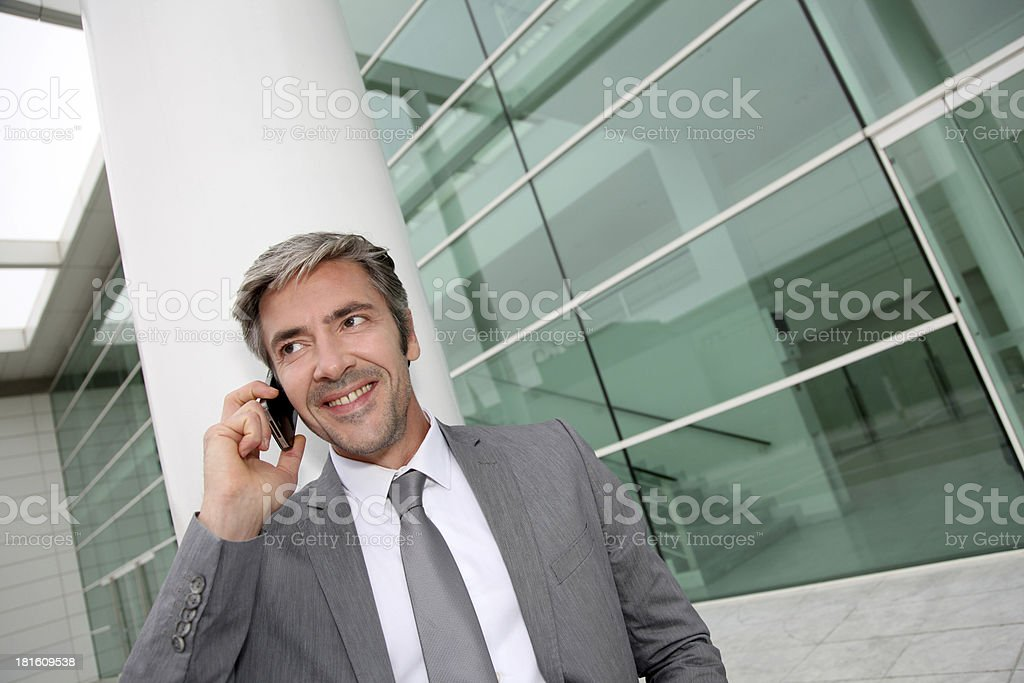 Smiling businessman with grey suit talking on smartphone royalty-free stock photo