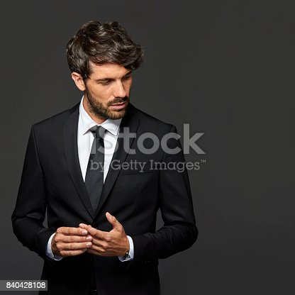 Serious businessman standing with hands clasped. Male executive is wearing suit. He is against black background.