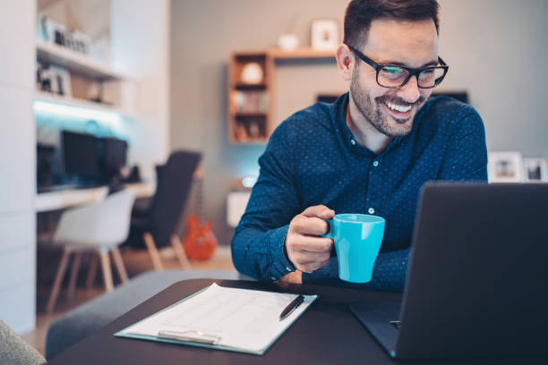 Smiling businessman with laptop and a cup of coffee at home stock photo