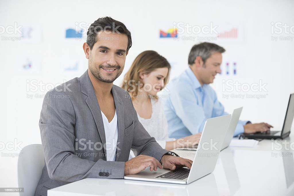 Smiling Businessman With Laptop At Desk royalty-free stock photo