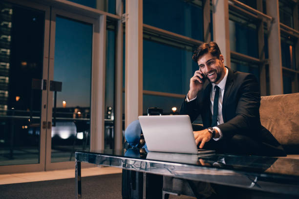 Smiling businessman with laptop talking on cellphone at the airport lounge stock photo