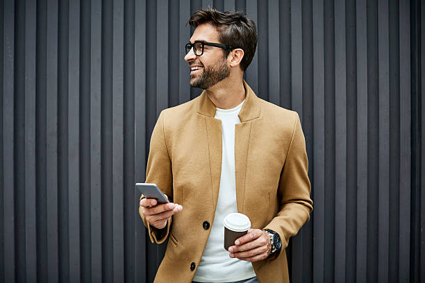 Smiling businessman with smart phone and cup stock photo