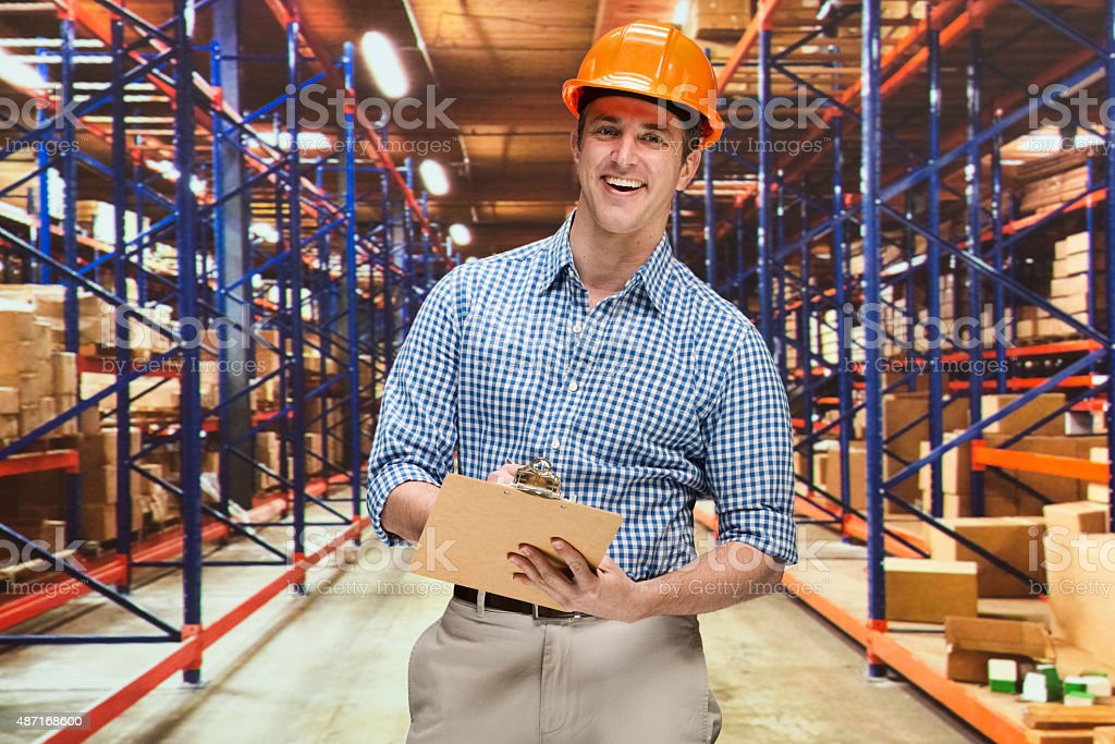 Smiling businessman working in warehouse stock photo